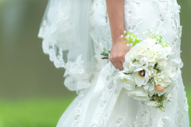 Bride holds a wedding bouquet. Bride wedding white dress in the garden. Nature Background royalty free stock photo