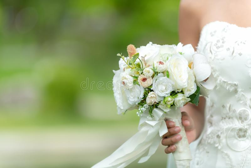 Bride holds a wedding bouquet. Bride wedding white dress in the garden. Nature Background stock image