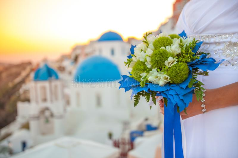 Bride holds wedding bouquet in white and green colors and blue decor against the backdrop of the sunset over Santorini, Greece stock photo