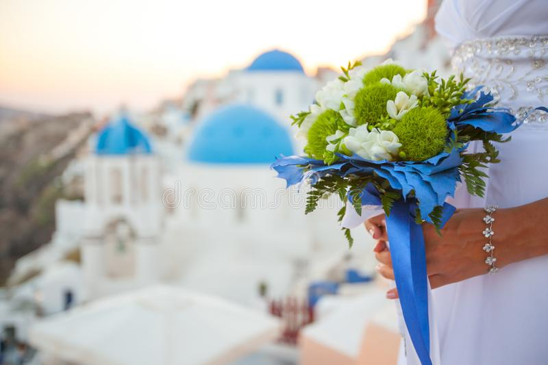 Bride holds wedding bouquet in white and green colors and blue decor against the backdrop of the sunset over Santorini, Greece stock image