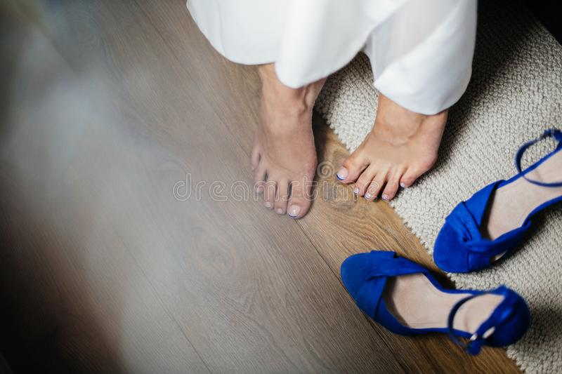 Bride holds the wedding shoes. Bride in elegant wedding dress and blue shoes. Concept of bride morning royalty free stock image
