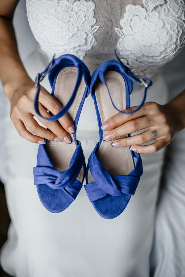 Bride holds the wedding shoes. In her hands royalty free stock photo