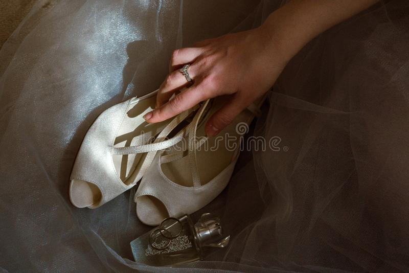 Bride holds wedding shoes and perfume. Bride holds in her hand wedding shoes, rings and perfumes stock photography
