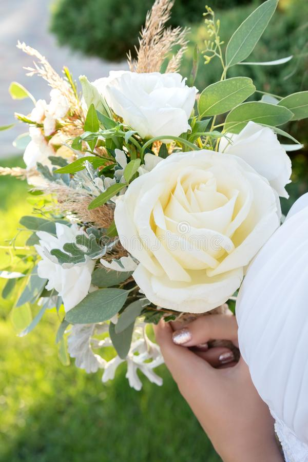 Bride holds a white wedding bouquet, close up.  stock photo