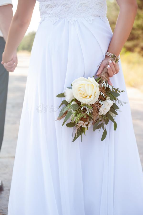 Bride holds a white wedding bouquet, close up.  royalty free stock image