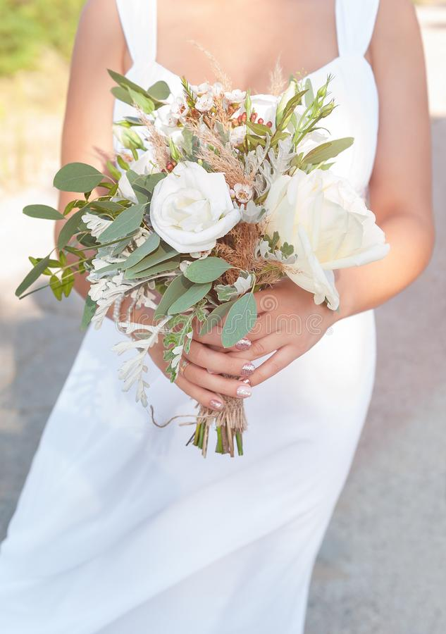 Bride holds a white wedding bouquet, close up.  royalty free stock photography
