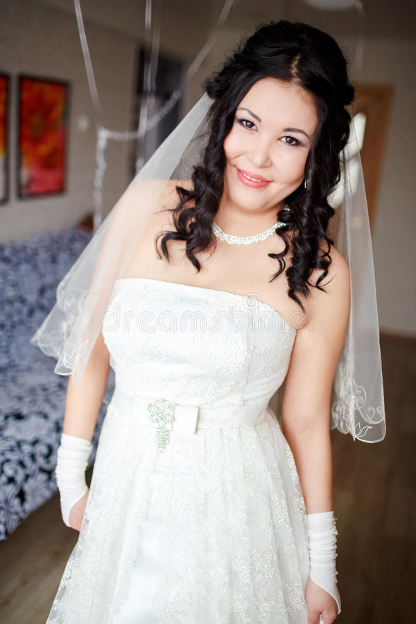 Bride at home ready for ceremony, waiting groom. She looks to camera smiling, balloons in the background. stock images