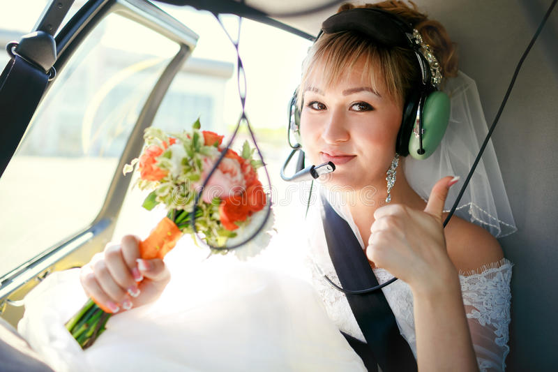 Bride inside helicopter preparing to fly, in headset, thumbs up. Bride inside a helicopter preparing to fly in the headset and with a wedding bouquet showing stock images