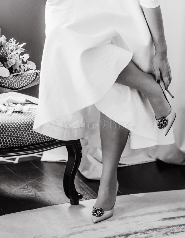 bride inside room morning gathering corrects shoes stock photo