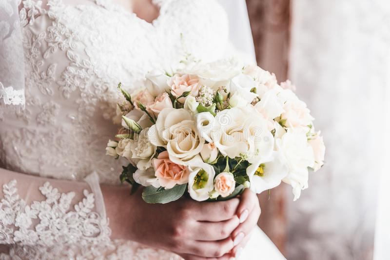 Bride keeps bouquet. Bride keeps delicate bouquet close royalty free stock image
