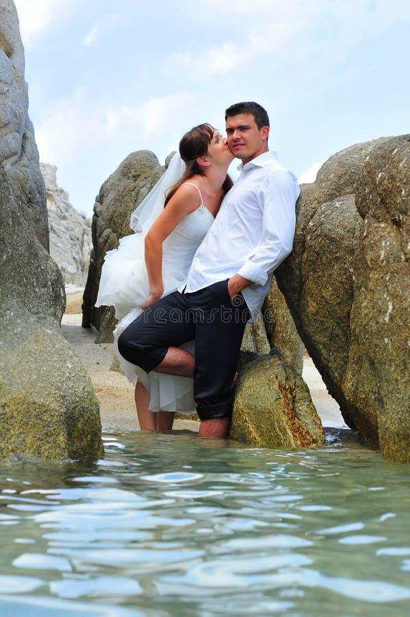 Bride kissing groom - trash the dress - sea scene stock photos