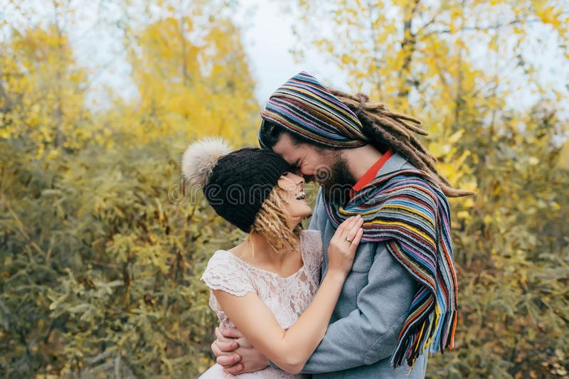 Bride in a knitted hat with a pom pom, hat covering her eyes. Groom in a colorful scarf. Happy young newlywed couple. Touching foreheads and noses in park stock image