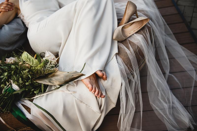 A bride is laying on the couch barefoot, her shoes are laying beside her. She is wearing a white wedding dress stock photo