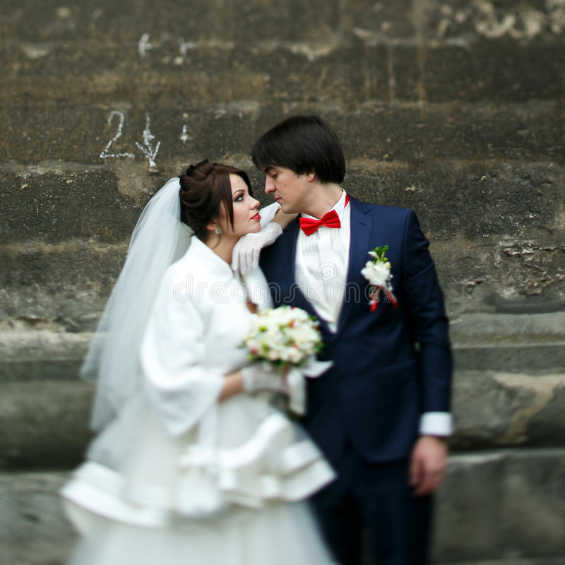 Bride leans on groom`s shoulder standing with him behind a stone royalty free stock photography