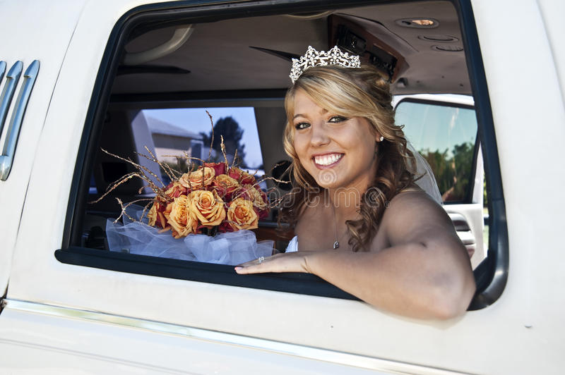 Bride in Limousine. A happy beautiful bride smiling in a limousine window royalty free stock photos