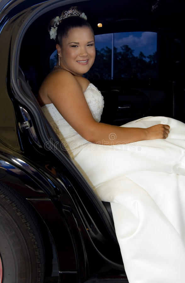 Bride in Limousine. A beautiful bride smiling in a black limousine stock photography