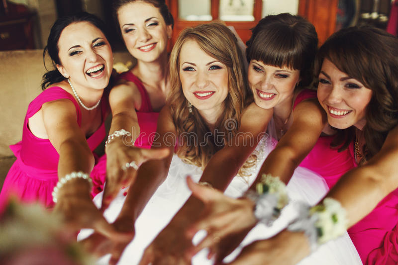Bride and bridesmaids reach their hands out and smile royalty free stock photo