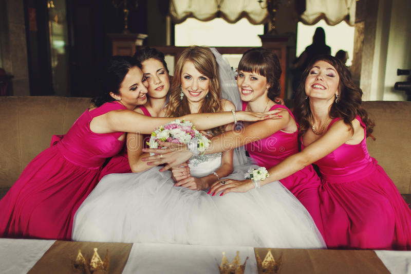 Bridesmaids in pink dresses hug a bride sitting on the sofa royalty free stock photo