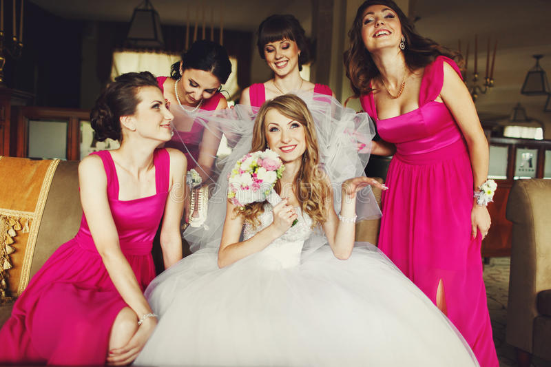 Bride lloks funny while bridesmaids in pink dresses hold her veil royalty free stock photo