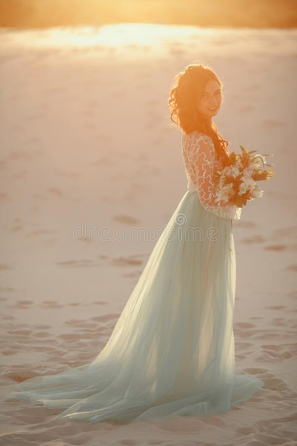 Bride with bouquet stands on sand in desert. Backlight and paste stock photos
