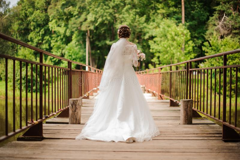 Bride in a long white lace dress walking on a wooden bridge stock photo