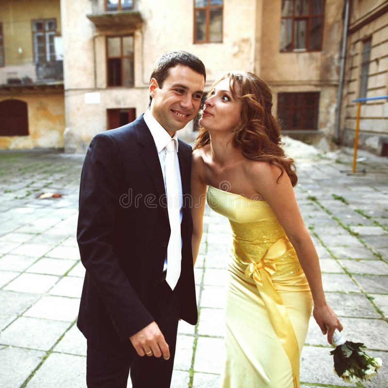 Bride looks funny while standing with groom. A royalty free stock photo