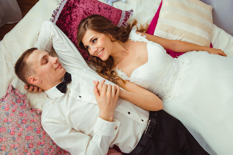 Bride looks at her handsome groom while lying on the bed stock photos