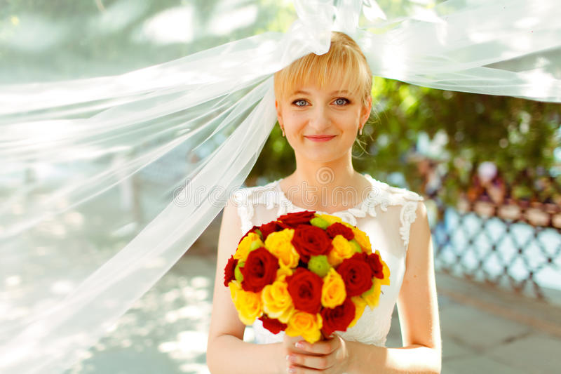 Bride looks shy holding a bouquet of yellow and red roses royalty free stock image