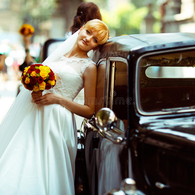 Bride looks tired leaning to an old retro car. Black and white photograph of a wedding couple kissing behind a retro car stock image