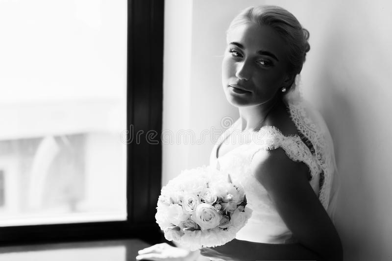 Bride looks tired sitting behind a window royalty free stock images