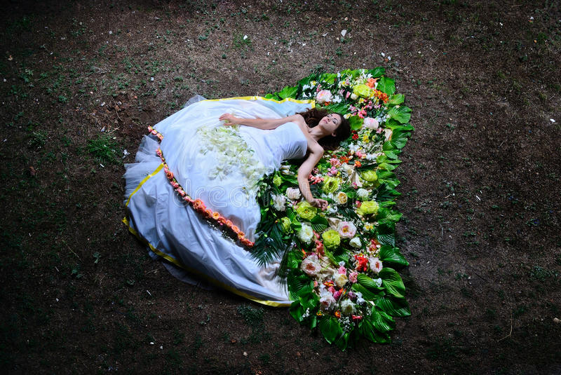Bride lying on the flowers in a wedding dress stock photos
