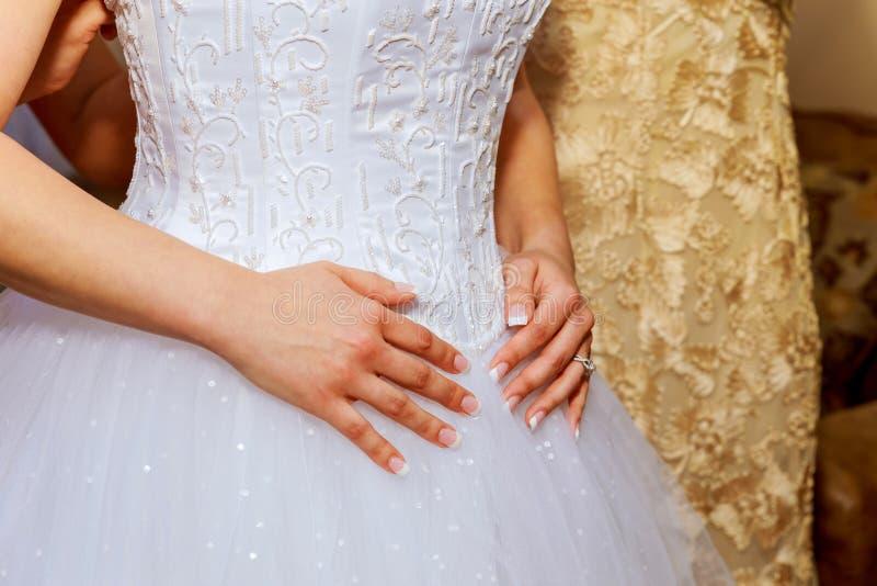 Bride& x27; manhã de s a noiva bonita nova no vestido de casamento branco uniu graciosamente a mão foto de stock