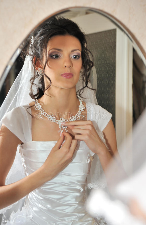 The bride before a mirror. The young girl in a wedding dress royalty free stock photo