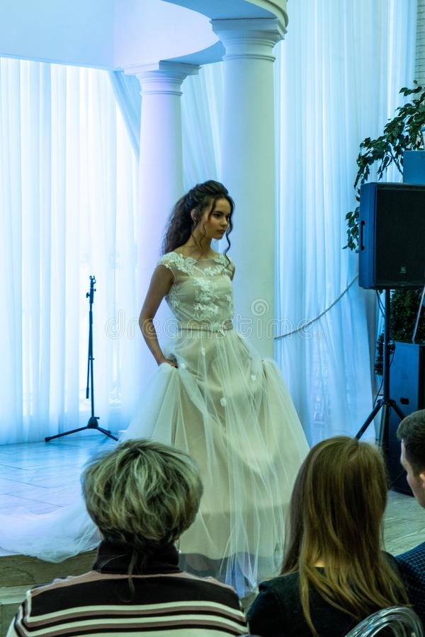 A bride model in a wedding dress walking down from a podium. At the exhibition Wedding hassle 2019 took place in Kirov, Russia royalty free stock photo