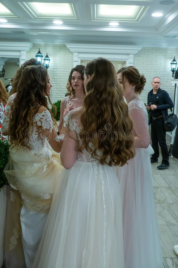 Bride models discussing something between their shows. Bride models take a rest between their shows at the exhibition Wedding hassle 2019 took place in Kirov royalty free stock photos
