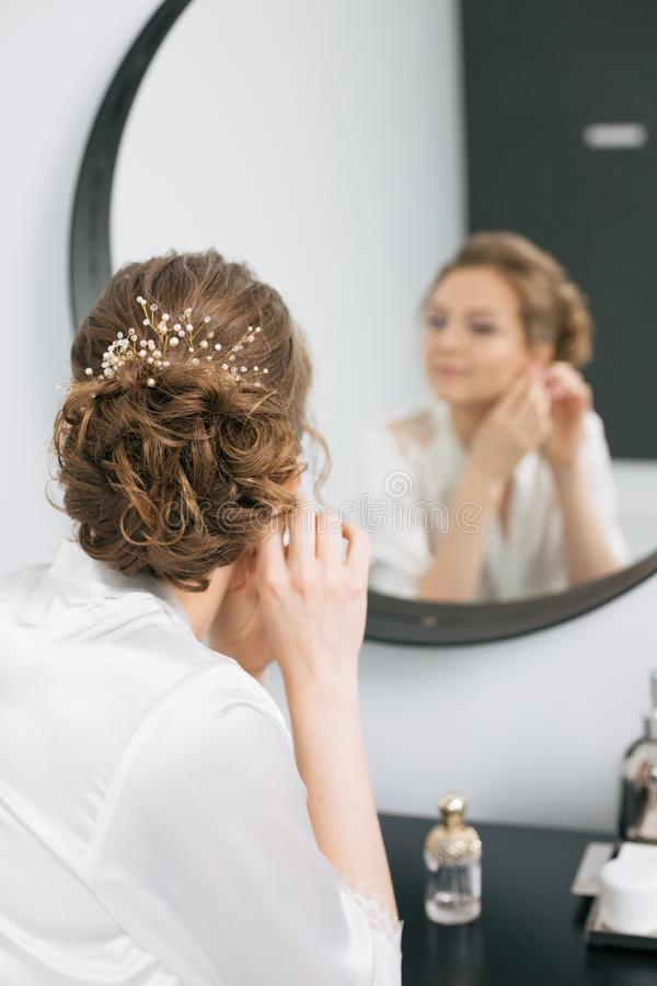 Bride morning looks mirror makeup accessories. Bride morning inside the room looks in the mirror round one straightens the makeup and clothes the accessories stock image