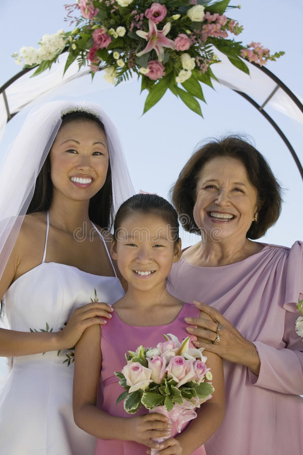 Bride With Mother And Flower Girl Standing Against Sky. Portrait of happy bride with mother and flower girl standing against sky stock photos