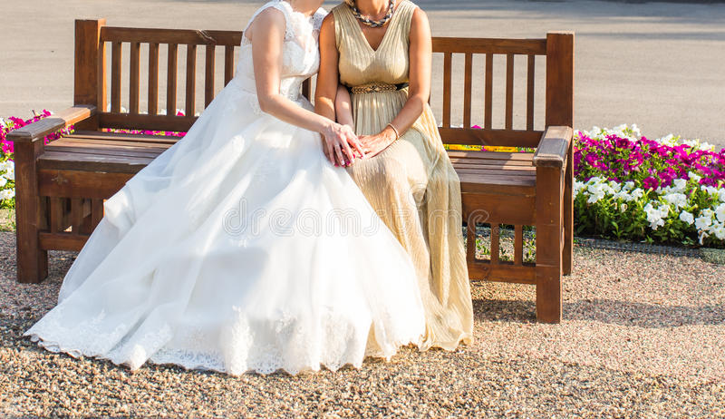 Bride With Mother sitting on a bench outdoors stock images