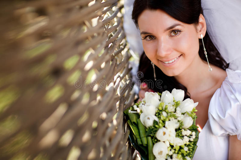Bride near the hedge. Young bride near the hedge royalty free stock photography