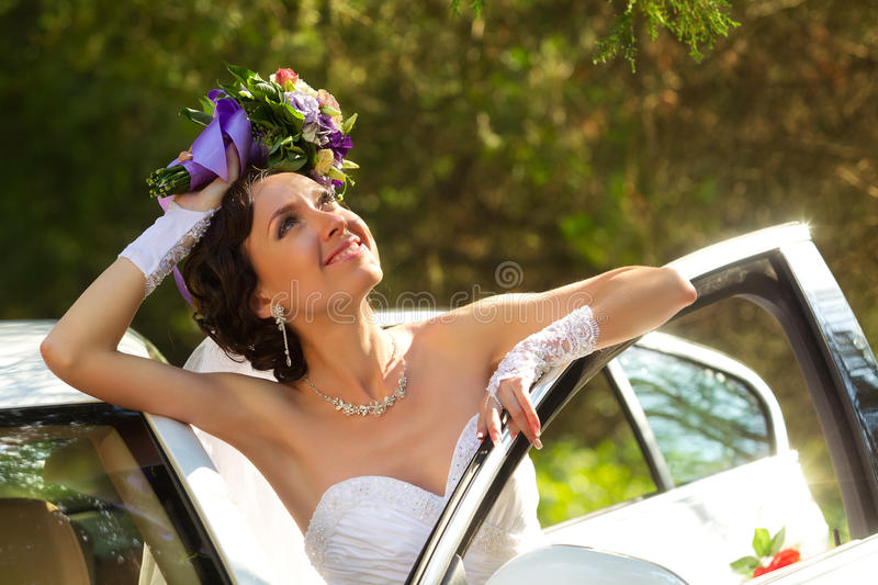 Bride next to a car royalty free stock photo