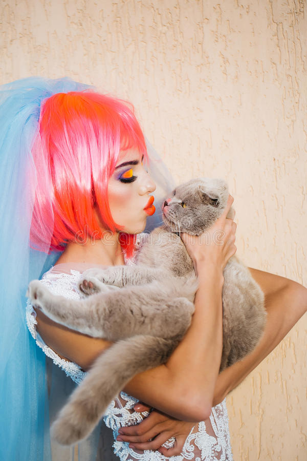 Bride with orange hair and cats. Young pretty woman with orange or pink hair and bright makeup on emotional face in white wedding dress and blue bride veil with stock photography