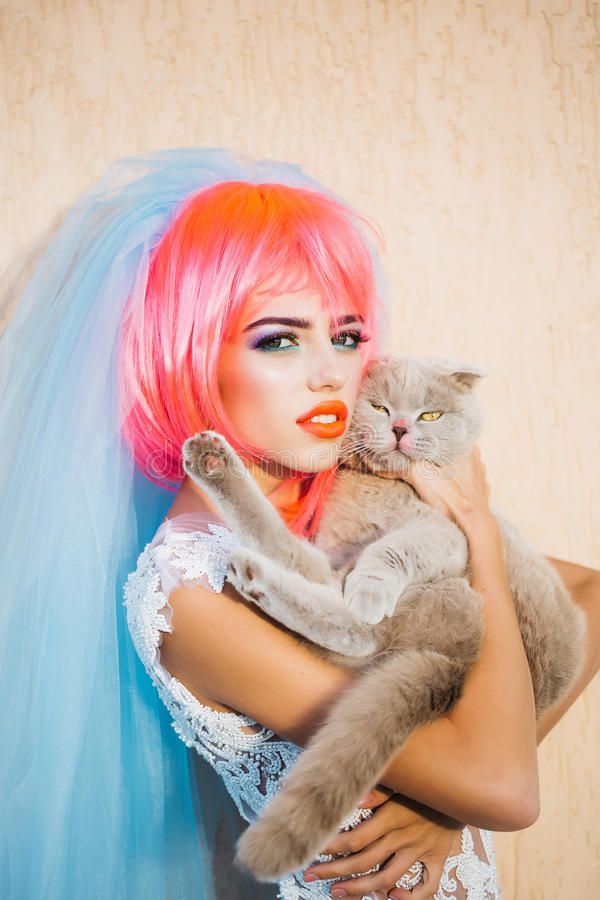 Bride with orange hair and cats. Young pretty woman with orange or pink hair and bright makeup on emotional face in white wedding dress and blue bride veil with royalty free stock image