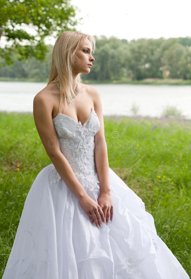 Bride in the park. Pensive bride in the park looking blankly into the distance royalty free stock images