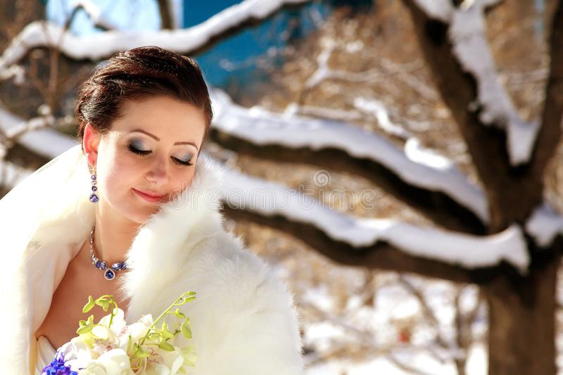 Bride in the park in winter. Portrait of young bride in winter Bride in the park in winter, woman, wedding, dress, adult, background, beautiful, beauty, bouquet royalty free stock images