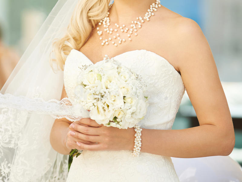 Bride with Pearl Jewelry. Holding bouquet royalty free stock photography