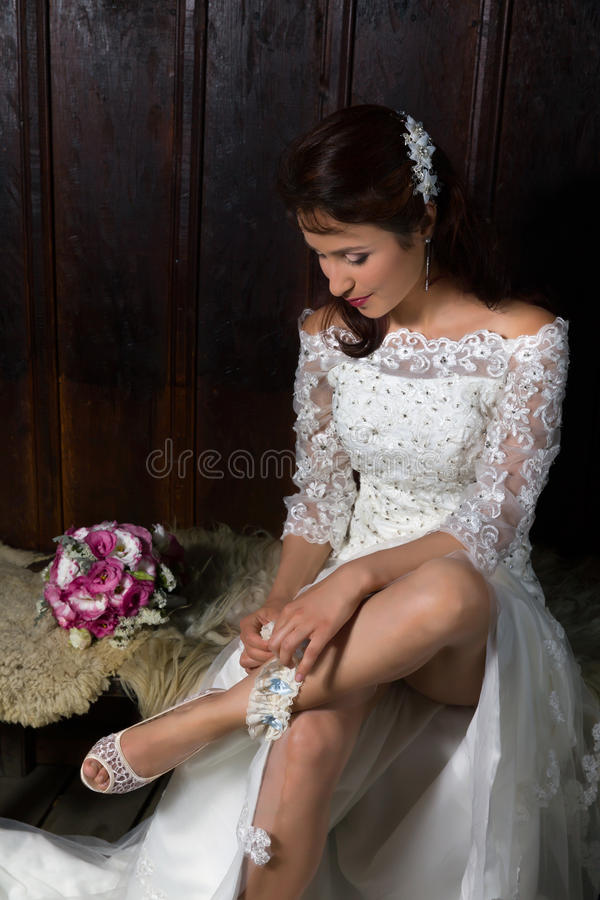 Bride playing with her garter. Pretty young bride playing with her garter royalty free stock photography