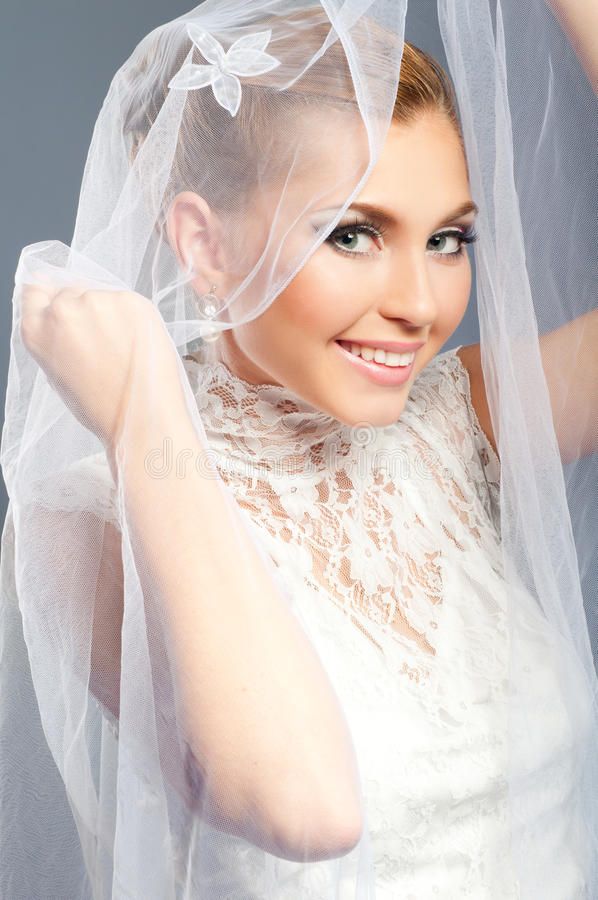 Bride portrait. Smiling bride peeks out from under the veil wedding royalty free stock photography