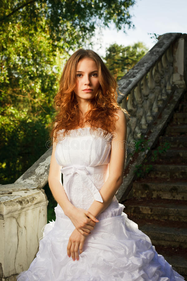Bride posing on old stairs royalty free stock image