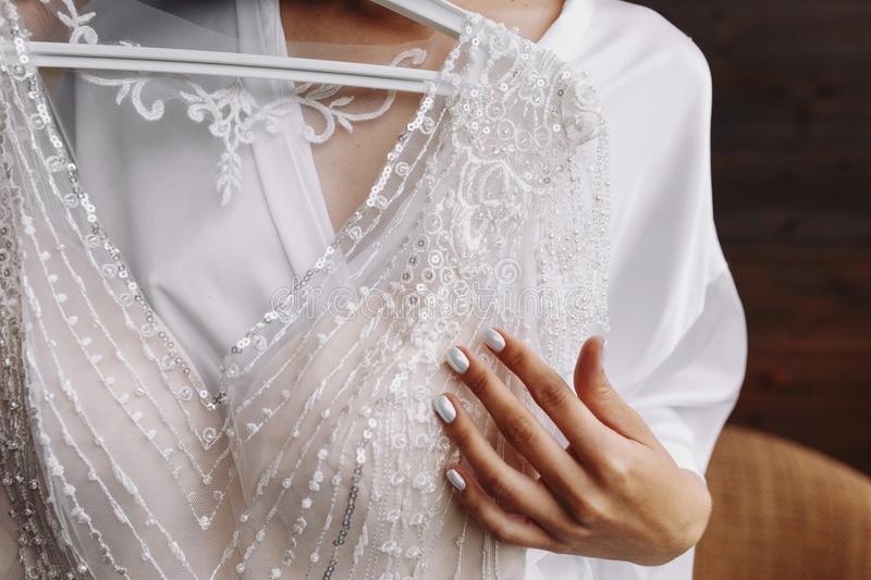 Bride.Preparations.Wedding.Manicure. Bride touch beads on your white wedding dress by hand with pearl nails. Close up stock image