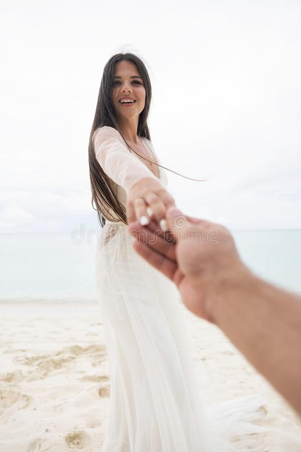 The bride pulls the hand of her fiance. A first-person view of a man stock photo